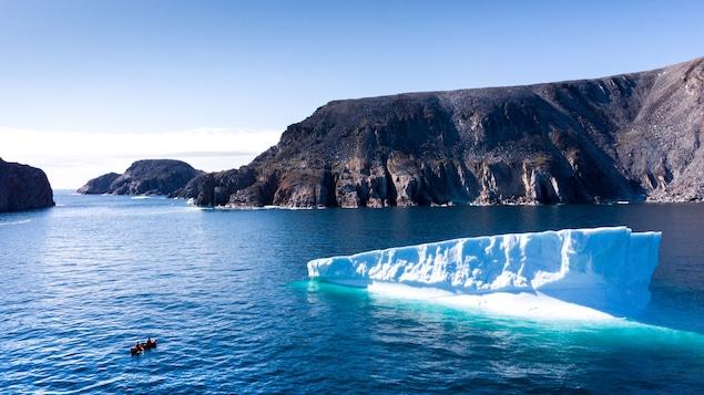 Un canot navigue près d'un iceberg.