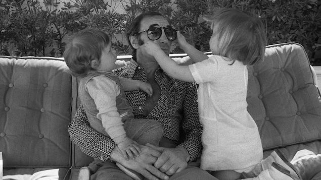 Charles Aznavour sur un canapé tient son garçon sur ses genoux et sa fille à ses côtés joue avec ses lunettes de soleil.