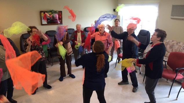 On voit des personnes âgées jonglant avec des foulards.