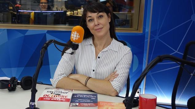 Une femme présente trois livres à la caméra dans un studio de radio.