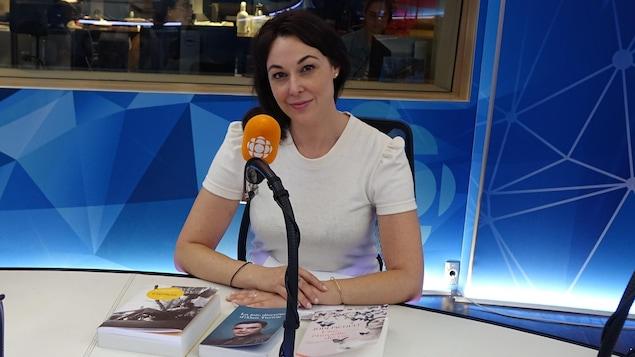 Une femme aux cheveux noirs portant un chandail blanc présente trois livres à la caméra dans un studio de radio.