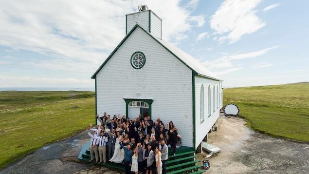 Les invités du mariage prennent la pose devant l'église