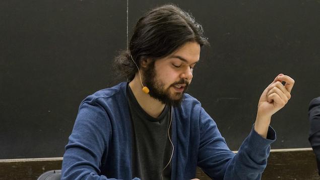 Nicolas Gaille en train de donner une conférence, assis derrière un bureau