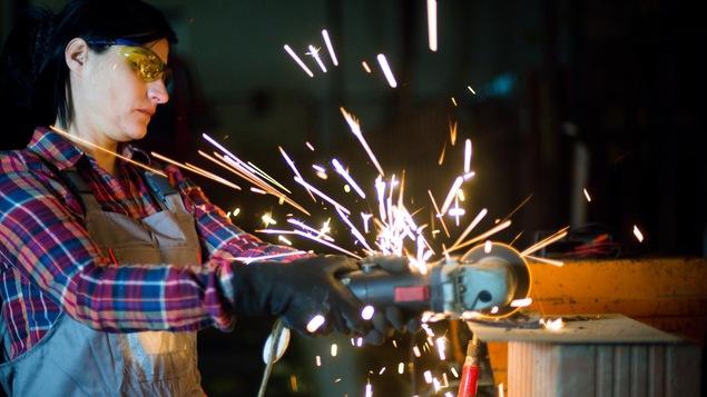Une ouvrière travaillant un morceau d'acier. Des flammèches tombent autour du morceau et de l'ouvrière.