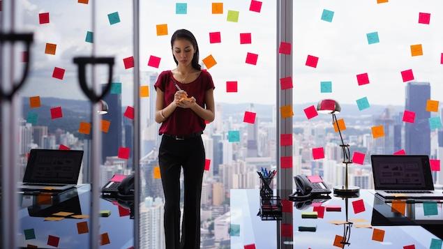 Une femme d'affaires occupée colle de nombreux papillons adhésifs sur les murs de son bureau.