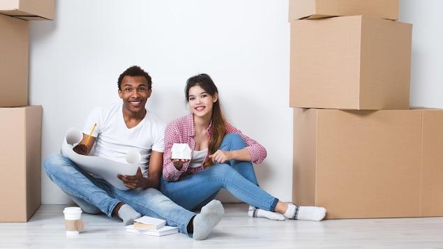 Un jeune couple mixte est assis par terre et sourit. Il est entouré de boîtes de déménagement car il arrive dans une nouvelle maison.