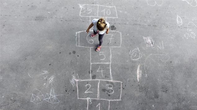 Une enfant joue à la marelle.