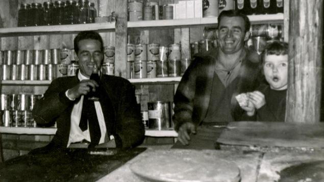 Photo en noir et blanc montrant deux hommes en train de rire en compagnie d'une petite fille. On voit des étagères remplies de conserves derrière eux.
