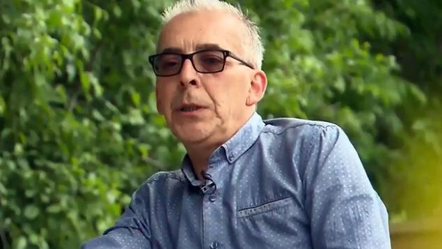 Un homme avec des lunettes noires est assis.