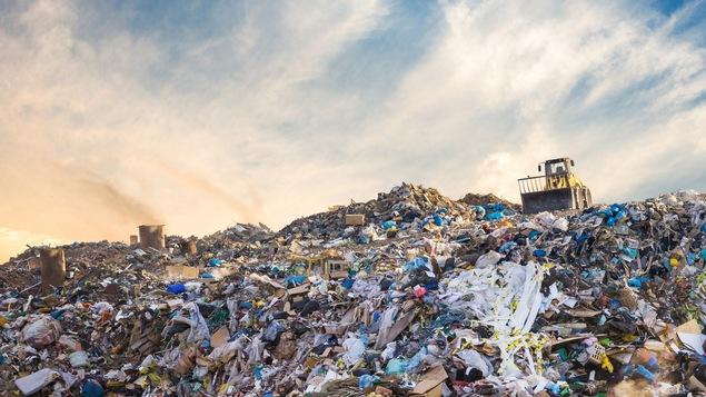 Un véhicule repousse des piles de déchets dans un dépotoir.