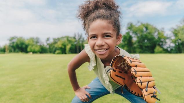 Une jeune fille afro-américaine, souriante, avec un gant de baseball dans un champ.