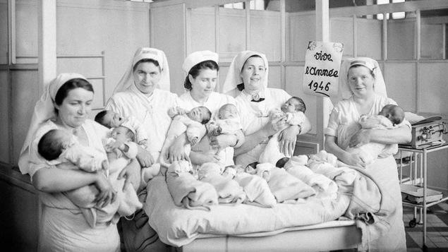 Des infirmières avec plusieurs bébé dans une pouponnière d'un hôpital à Paris en 1946