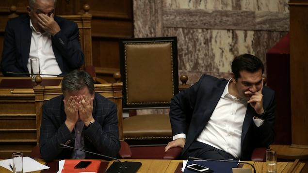 Le Premier ministre grec Alexis Tsipras et le ministre des Finances, Euclid Tsakalotos, réagissent lors d'une session parlementaire avant le vote sur la dernière série d'austérité.