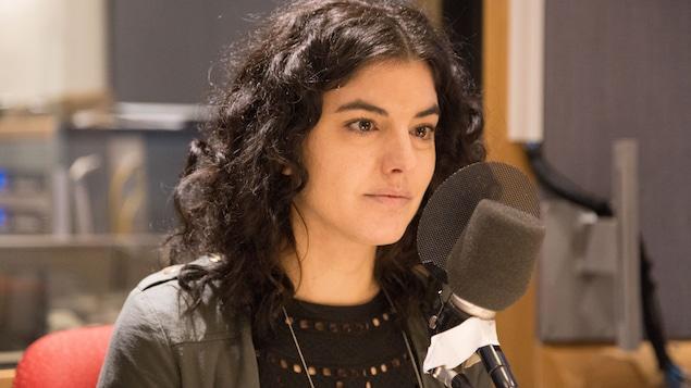 Karine Péloffy, assise derrière un micro