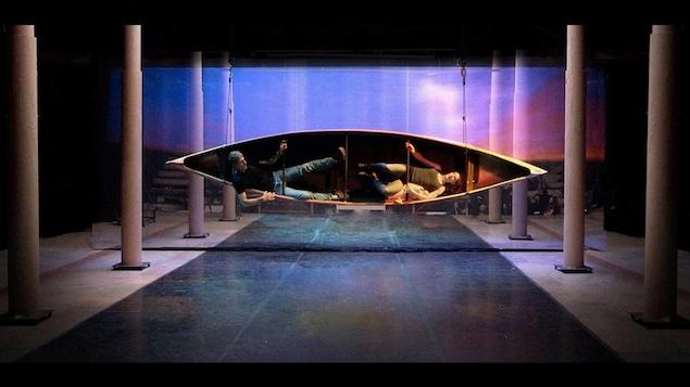 Deux comédiens sont couchés au fond d'un canot, suspendu par le côté