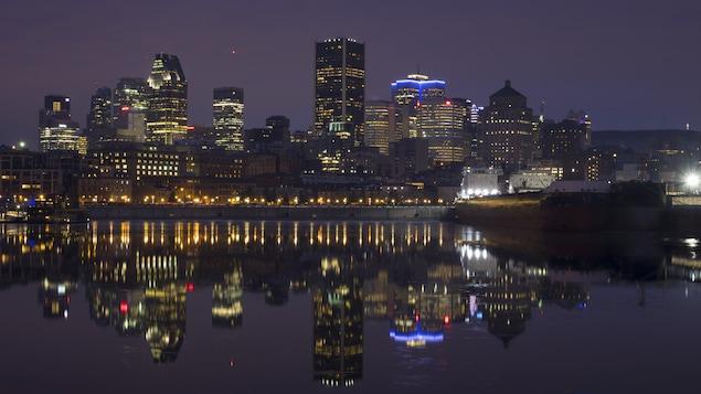 Les édifices de la ville de Montréal se reflètent dans les eaux du Vieux-Port à l'aube d'une journée de janvier.