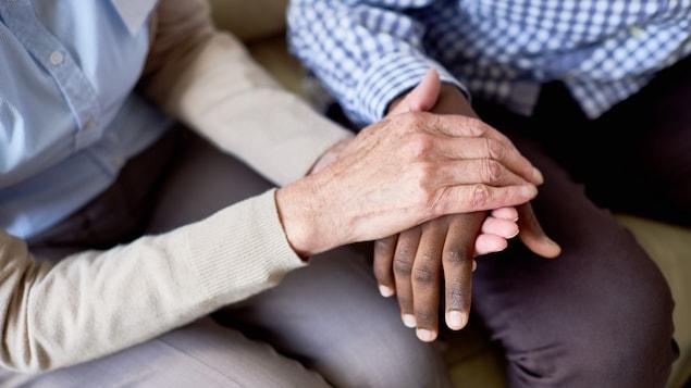 Les mains d'une personne d'un certain âge, offrant un support moral en tenant les mains d'un jeune, à la peau noire.