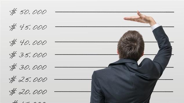Un homme de dos qui indique le niveau fictif d'un revenu minimum sur un tableau gradé de 20 000 $ à 50 000$.