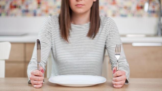 Une jeune femme mécontente est assise devant une assiette vide et tient des ustensiles dans ses mains.