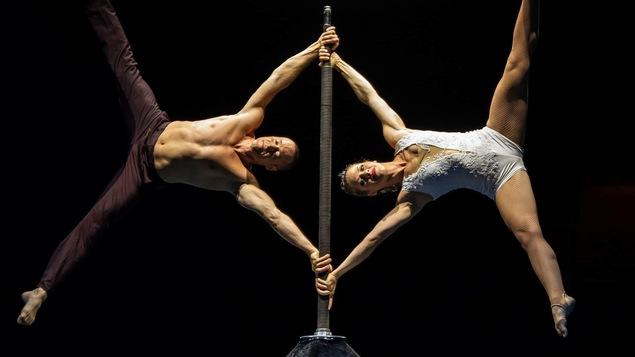 Un homme et une femme qui se tiennent à l'horizontal sur une perche verticale.