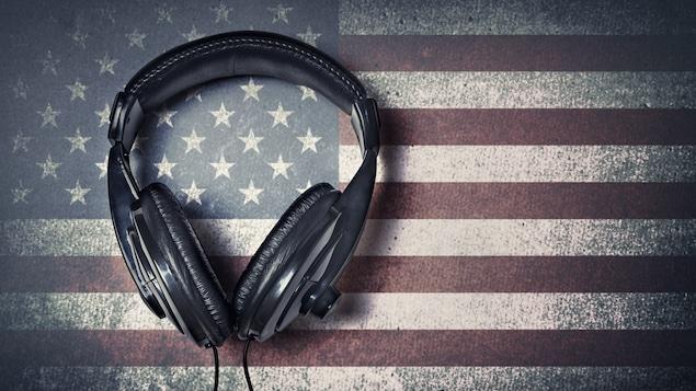 Une paire d'écouteurs, au-dessus d'une infographie d'un drapeau américain