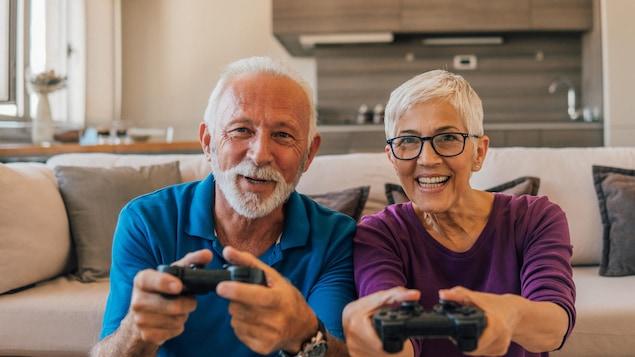 Une couple d'aînés joue à un jeu vidéo.