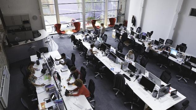 Des employés travaillent dans une aire ouverte.