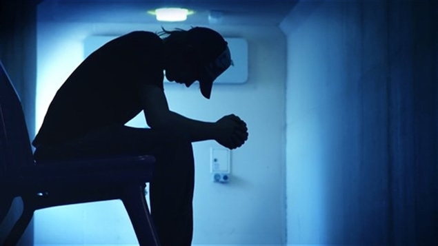 Un homme assis dans l'ombre, la tête penchée et visiblement en détresse