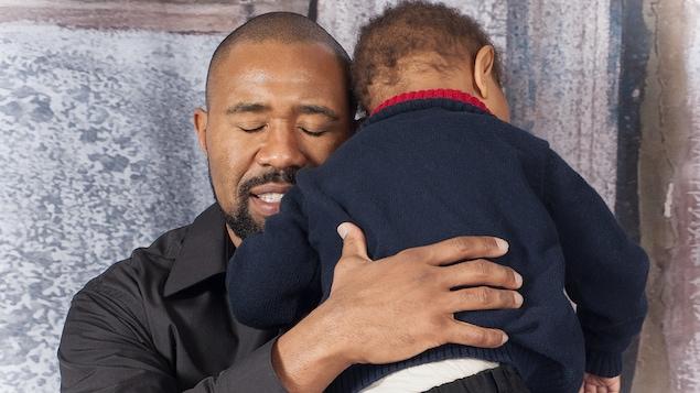 Un père console son fils qui vient de se blesser.