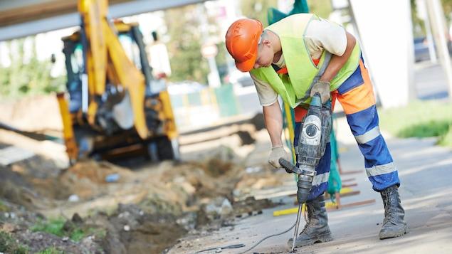 Un ouvrier utilise un marteau-piqueur.