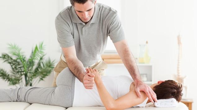 Un physiothérapeute s'exerce sur une patiente.