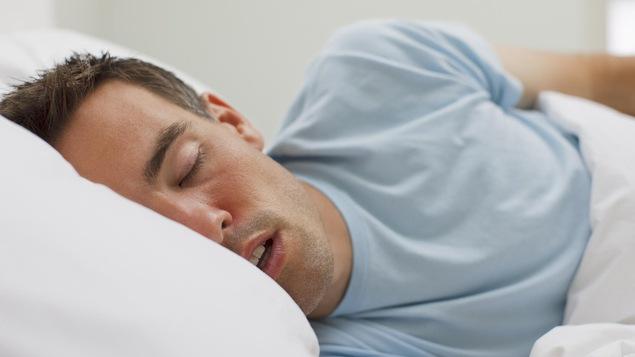 Un homme dort dans son lit.