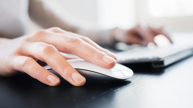 Un homme utilise un ordinateur au bureau.