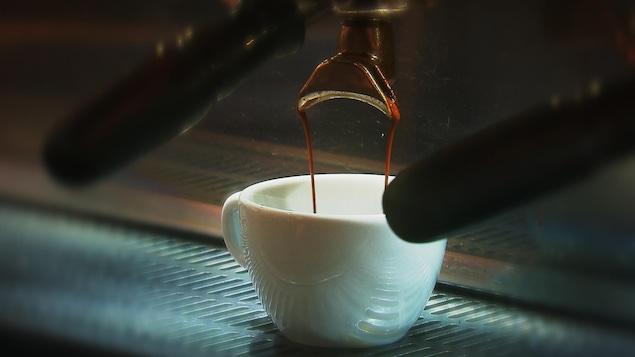 Tasse de café en céramique dans laquelle coulent deux minces filets d'espresso.