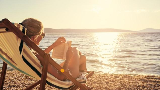 Une femme lit sur une plage pendant ses vacances.