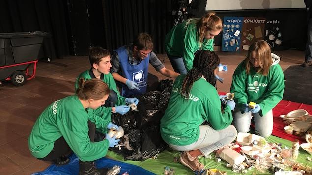 Des élèves avec ses gants de plastique, qui font le tri des sacs de poubelles