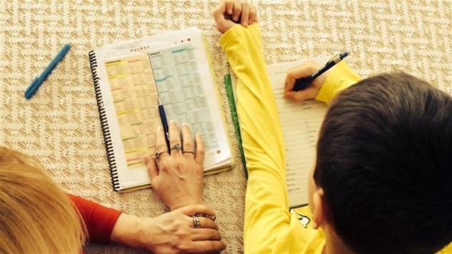 Une adulte aide un enfant à faire ses devoirs