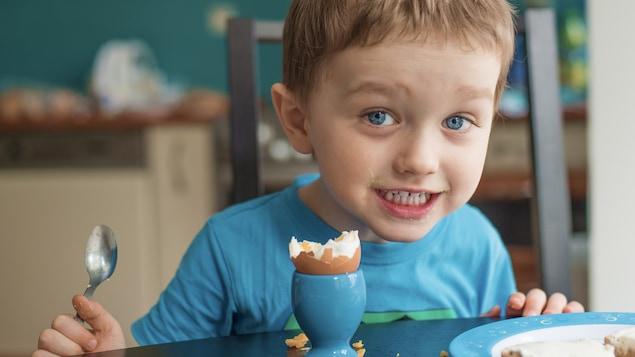 Souriant, un jeune garçon savoure une oeuf mollet dans sa coquille pour le déjeuner.