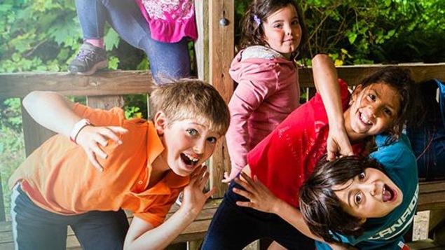Des enfants se penchent dans tous les sens en riant.