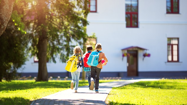 Trois enfants qui marchent vers une maison en après-midi.
