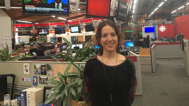 Une femme est photographiée dans une salle des nouvelles.