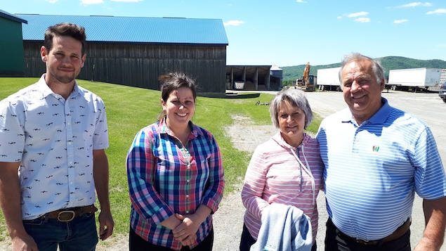 Une famille composée des parents et de leurs deux enfants, un homme et une femme dans la vingtaine, posent devant une ferme.