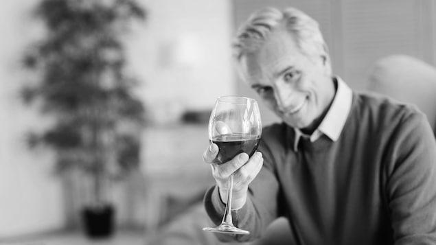 Un baby-boomer tend un verre de vin rouge vers la caméra.
