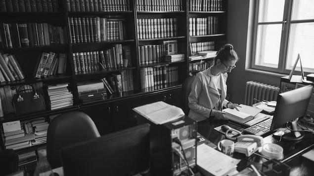 Une jeune secrétaire feuillette un livre, assise devant un écran d'ordinateur.