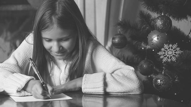 Une jeune fille écrit une lettre au père noël.