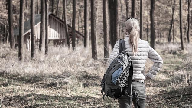 Une femme approche son refuge dans la forêt.