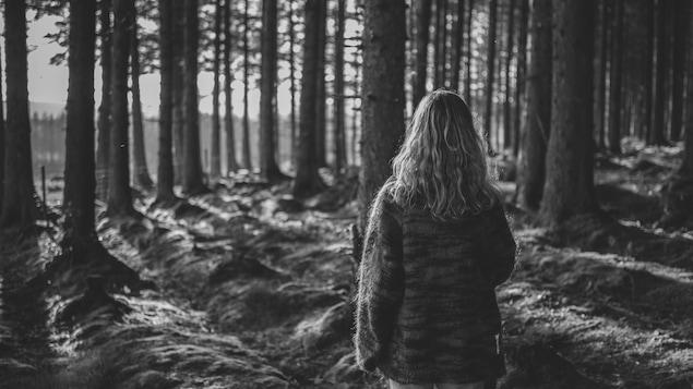 Une jeune femme marche seule dans la forêt. Pour certains, cette image a un effet apaisant. Pour d'autres, un effet angoissant.