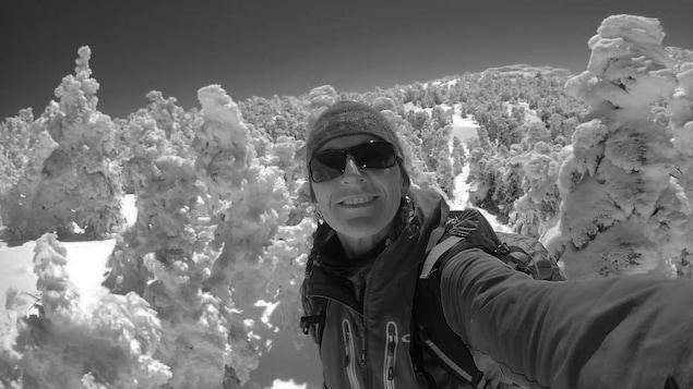 L'alpiniste Nathalie Fortin prend un égoportrait, sur le sommet d'une montagne enneigée.