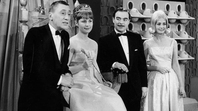 L'animateur Roger Baulu prend la pose avec Marie-Claude Lévesque qu'on voit assise sur un trône coiffée d'un diadème, l'annonceur Henri Bergeron et l'hôtesse Lucie Gauthier.