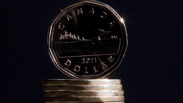 Un dollar canadien en équilibre sur une pile d'autres sous.